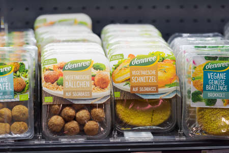 Regensburg, Germany - 2021 02 05: Refrigerated section with packs of different vegetarian and vegan convenience food of brand dennree behind glass doors on display in German organic super market