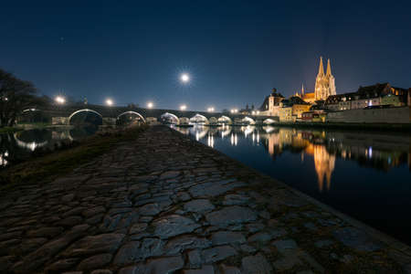 Moon in clear starry sky over Regensburg in Bavaria with landmarks Stone bridge and cathedral on the Danube river
