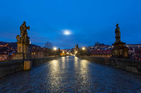 View from the Charles bridge in Prague over the Vlatva river at night with full moon Banco de Imagens