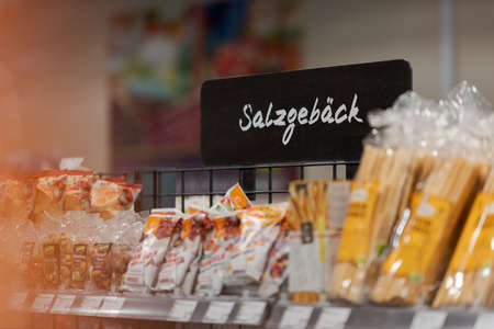 Munich, Germany - 2021 02 05: Sign over shelf in german organic supermarket with german word for salty snacks Editorial