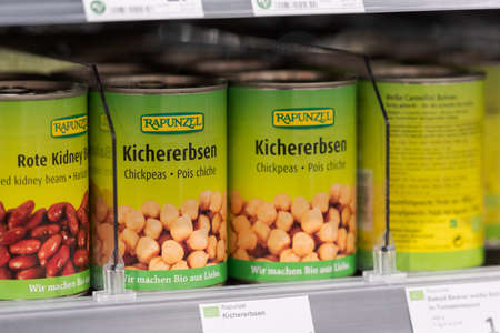 Munich, Germany - 2021 02 05: Tinned chickpeas of brand Rapunzel in shelf on display in german organic supermarket