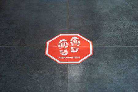 Munich, Germany - 2021 02 05: Stop sign on floor in german organic supermarket with german words for please wait