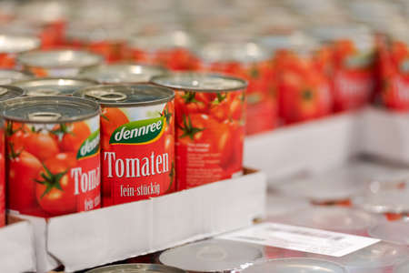 Munich, Germany - 2021 03 05: Tinned tomatoes of brand dennree on display in german organic super market Editorial