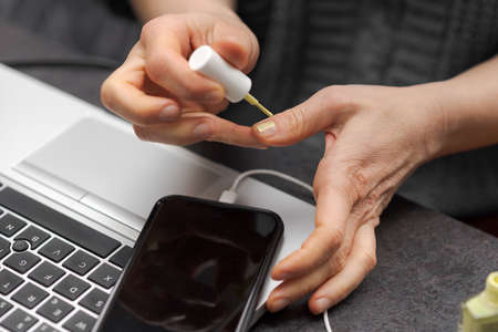 Female or male hands applying green nail polish on fingernails as stress relieve from work at desk in home office near laptop computer and smartphone