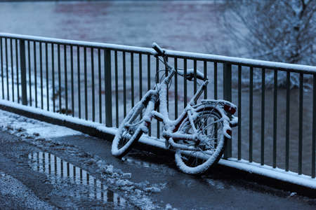 Abandoned and forgotten bike leaning on bridge railing without saddle in winter with snow