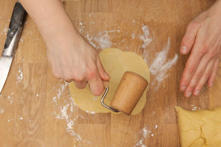 High angle view of human hands rolling out a small patch of pastry dough on wooden kitchen table with small wooden rolling pin Banco de Imagens