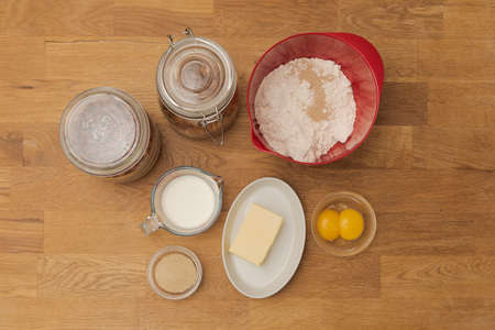 Flat lay of typical baking ingridients for pastries like milk, butter, flour, nuts, egg yolk and sugar standing on wooden table in glasses and bowls