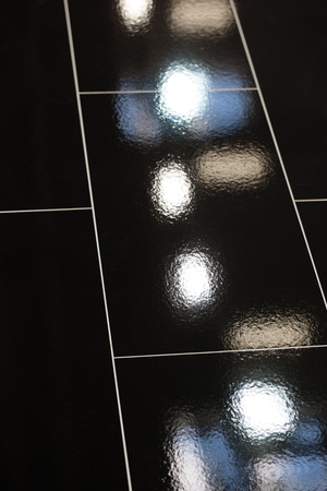 lacquered: Detail of the reflections of white, blue and brown lamps in a black tiled floor with white joints. Stock Photo