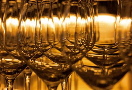 Detail opname van velen, een na de andere rij, lege wijnglazen in gouden backlight van een restaurant.