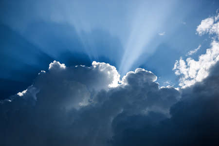 impressive: Impressive dark blue cloudscape with white cloud edges and sunbeams Stock Photo