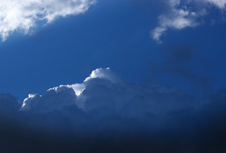 storm cloud: Impressive dark blue storm cloud with a small white cloud edge and some bright shreds of clouds Stock Photo