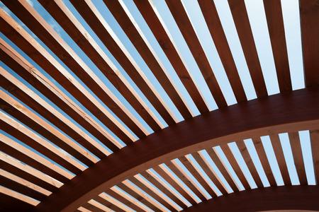 半円形の透かし彫りのデザインと木製のスラットの近代的な建築工事