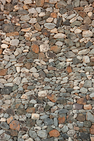 horizontal format: Detail shot of a Canarian natural stone wall with multicolored, small to medium stones in horizontal format.