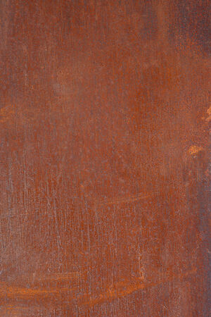 nuances: Abstract pattern of a rusty metal plate in orange brown with light scratches and blue nuances.