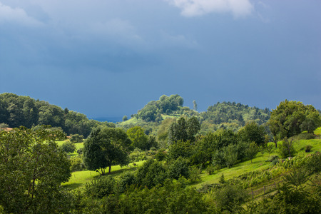 Stormy atmosphere in the Swabian Alps with sunny landscape and dark blue thunderclouds in the background. Stock Photo