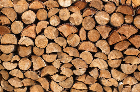 quartered: Stacked logs of spruce with whole, half and quartered logs with bark Stock Photo