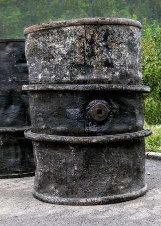 asphalting: An old barrel of tar stands at a construction site near the forest.