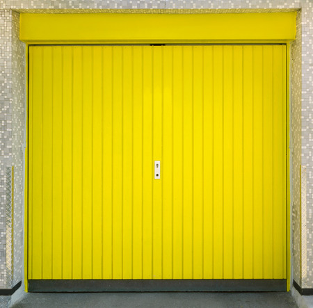 Yellow garage door in a tiled facade in a small town in Germany photo