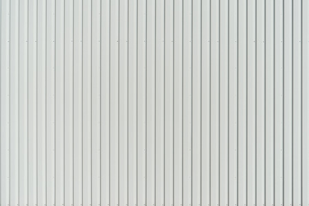 perpendicular: New white wall paneling made of aluminum wall profile with vertical structure. Stock Photo