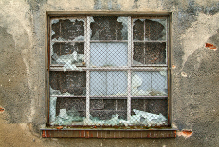 kaput: Barred, broken window in the ruins of an old industrial building