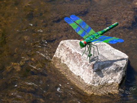tinkered: An artificial, slightly weathered, blue and green dragonfly sits as a decoration on a stone by the river