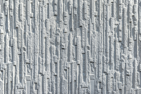 perpendicular: Older white concrete wall with strong relief in a vertical structure. Stock Photo