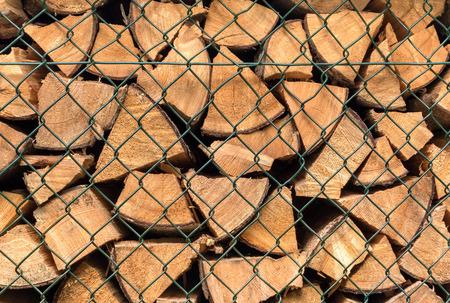 Stacked firewood is behind a dark green diagonal grid Zdjęcie Seryjne