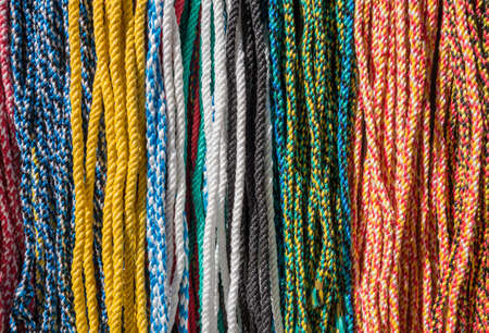 eachother: Multicolored ropes hang close next to eachother in a row Stock Photo