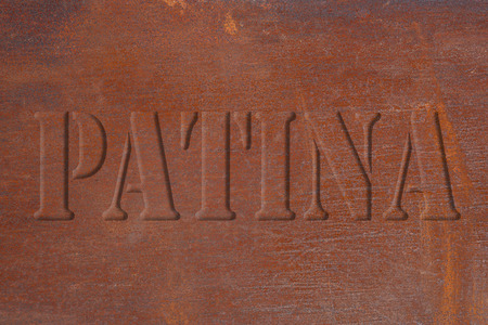 nuances: Abstract pattern of a rusty metal plate in orange brown with light scratches and blue nuances and the inscription PATINA in relief.