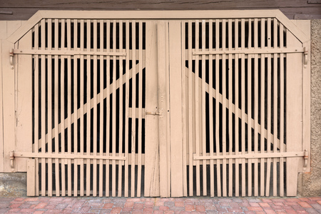 Old light brown gate of wooden slats in a barn, shed, garage photo