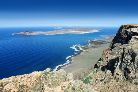 neighbouring: Lanzarote - View from Famara-Cliff near Guinate to the neighbouring island of La Graciosa. In the background the uninhabited islands Montana Clara and Isla de Alegranza.