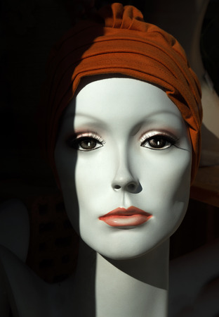Noble face of a female mannequin with a brown headgear
