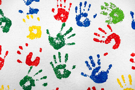 Colorful hand prints in green, red, blue and yellow on a white wall photo