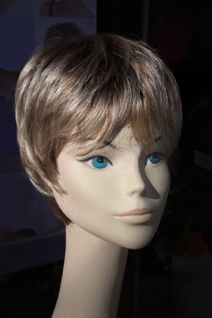 Head of a mannequin with blond short hair and blue eyes photo