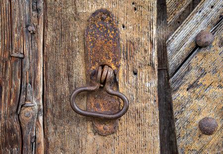 manipular: Detalle de un anillo ovalado de metal oxidado en una vieja puerta de madera marrón