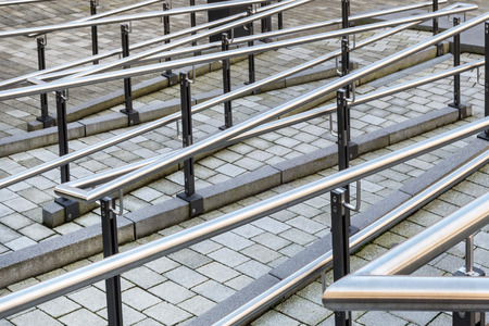 barrier free: Urban paved footpath with a maze of silver handrail Stock Photo