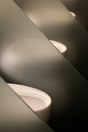 Three white toilet bowls with small gray partitions photo