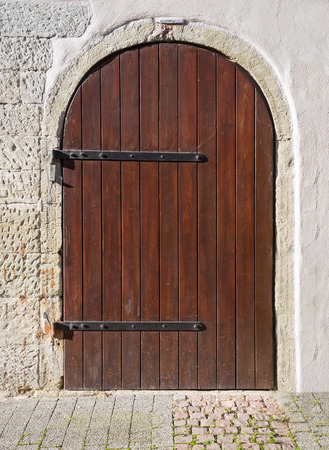 mountings: Old, round, dirty wooden door with two iron mountings in a bright facade with stone arch