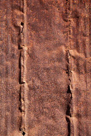 Detail shot of an old, broken metal surface with vertical, raised lines and strong patina. Stock Photo