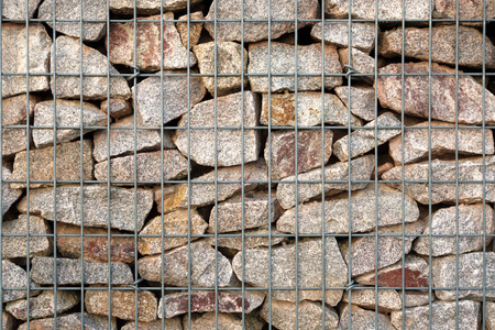 gabion: Detail of a gabion - grid basket with gray natural stones - which was built as a modern fence