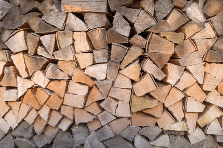 Woodpile with firewood in different color shades from gray to brown