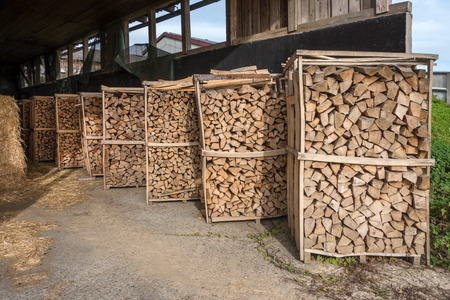 Several, diagonal one after the other positioned firewood racks in an open barn