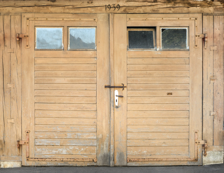 Old light brown garage door made of wood with four small windows, built 1939 in Oberndorf, Germany.