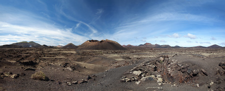 volcanic landscape: Panoramic shot of the volcanic landscape around the volcano Montana del Cuervo. In the background the Timanfaya National Park - Lanzarote, Canary Islands, Spain.