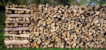 Panoramic shot of a wide woodpile with different stacking patterns