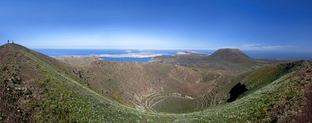 Lanzarote - Panoramic view from the blooming crater rim in the caldera of the volcano Los Helechos. Behind the Monte Corona, off the coast the islands of La Graciosa, Montana Clara and La Alegranza.