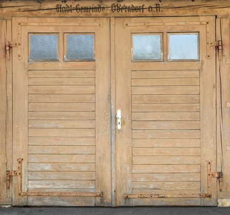 close p: Old, slightly weathered, light brown garage door made of wood with four small windows and the United inscription Borough Oberdorf (town municipality Oberndorf aN)