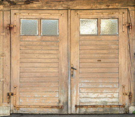 close p: Old, light brown, dirty and weathered wooden garage door with four small glass windows and rusted iron fittings.