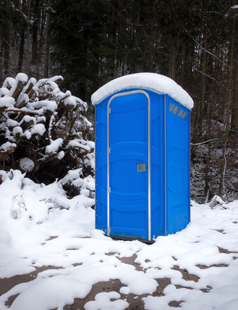 latrine: Snow-covered, blue, portable toilet on a winter day in the snowy forest