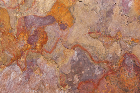 Abstract pattern of a stone plate in rust, orange, beige and purple. The slab is part of a wall covering in La Gomera, Spain.